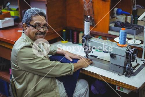 Portrait of smiling shoemaker using sewing machine