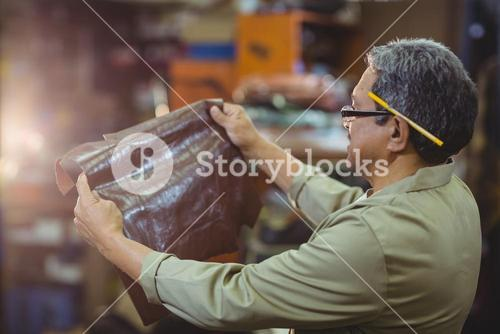 Shoemaker examining a piece of leather