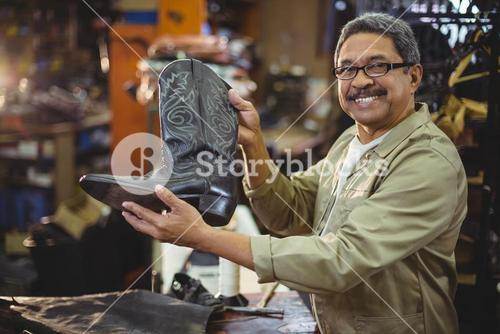 Portrait of smiling shoemaker holding a leather boot