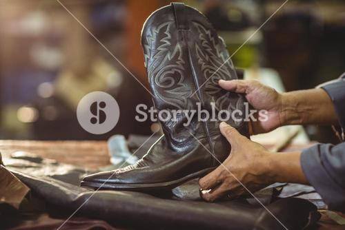 Shoemaker holding a leather boot