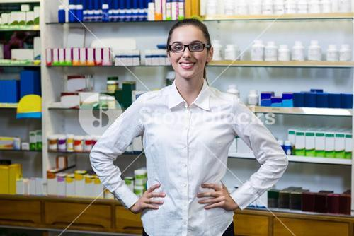 Pharmacist standing with hand on hip in pharmacy