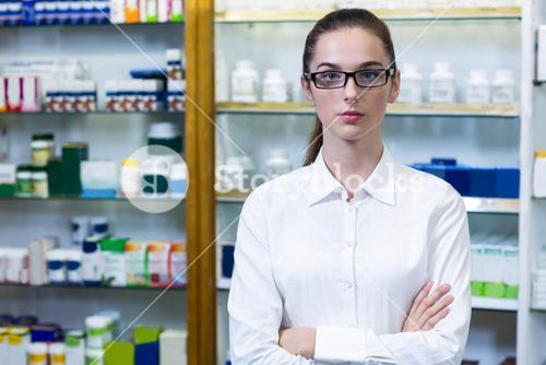 Pharmacist standing with arms crossed in pharmacy