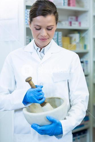 Pharmacist grinding medicine in mortal and pestle