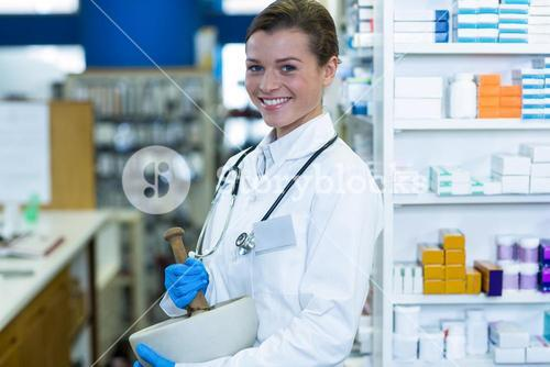 Pharmacist grinding medicine in mortal and pestle at pharmacy