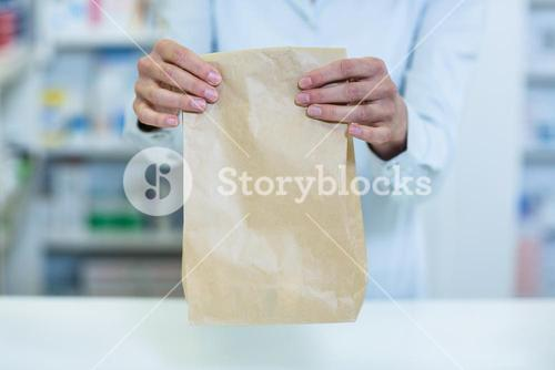 Pharmacist holding a medicine package in pharmacy