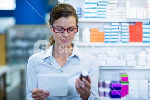 Pharmacist checking at prescription and medicine container