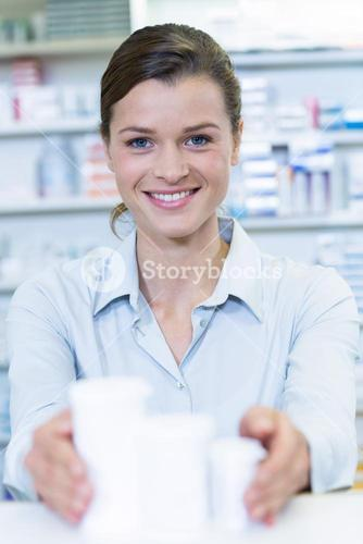 Smiling pharmacist holding medicine container in pharmacy