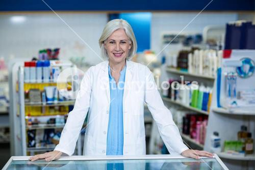 Pharmacist standing at counter in pharmacy