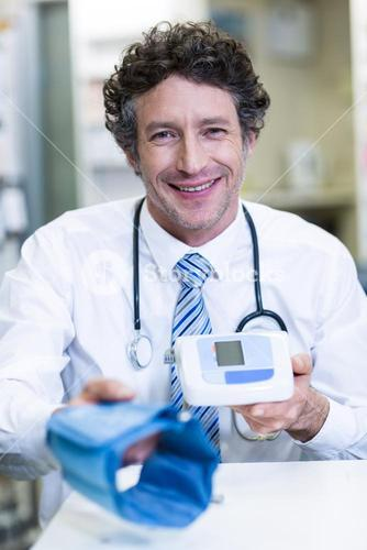 Pharmacist holding blood pressure monitor in pharmacy