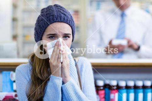 Customer covering her nose while sneezing in pharmacy