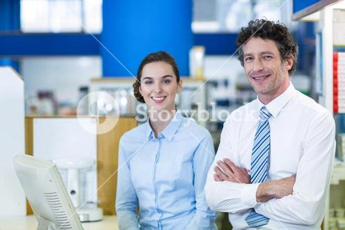 Smiling pharmacists standing at counter in pharmacy