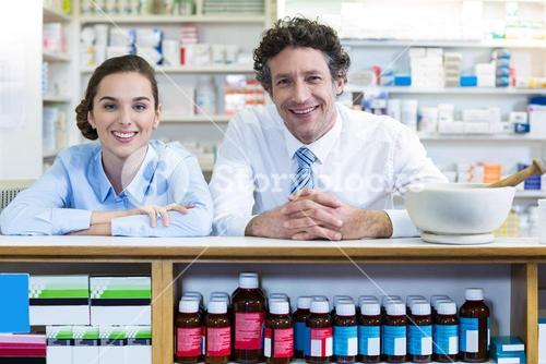 Smiling pharmacists leaning at counter in pharmacy