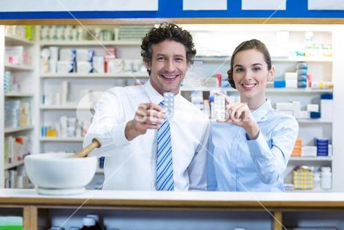 Smiling pharmacist showing medicine in pharmacy