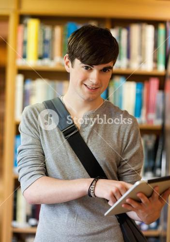 Portrait of a smiling student using a tablet computer