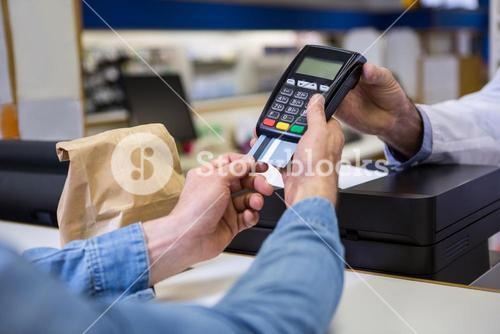 Customer entering pin in payment terminal machine