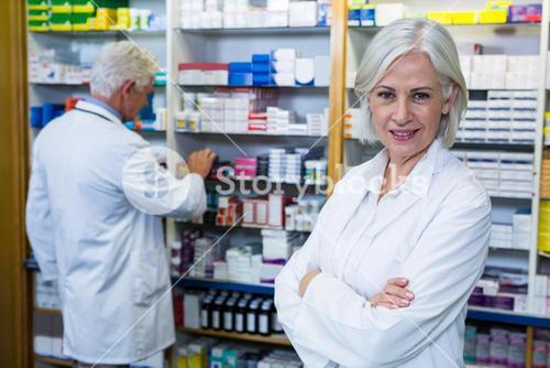 Pharmacist standing with arms crossed and co-worker checking medicines