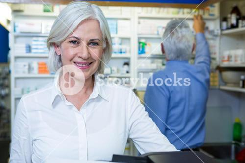 Pharmacist smiling and co-worker checking medicines
