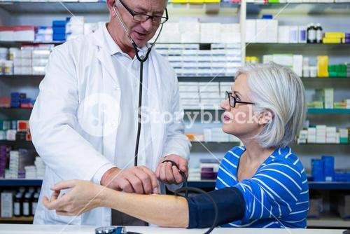 Pharmacist checking blood pressure of customer