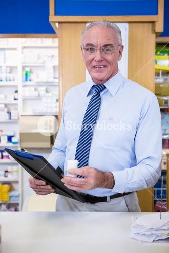 Pharmacist holding a medicine container and clipboard