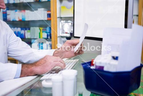 Pharmacist making entries on computer