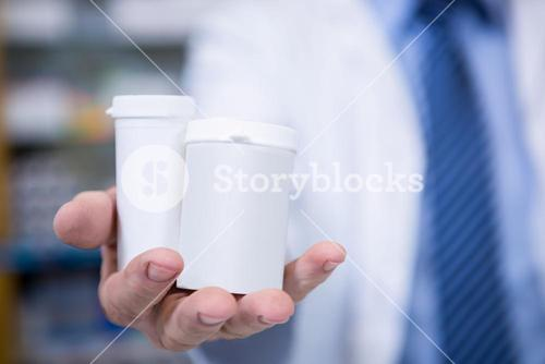 Pharmacist holding bottles of drug