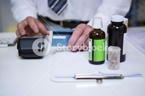 Pharmacist using payment terminal machine