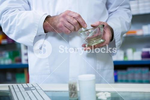 Pharmacist grinding medicine with mortar and pestle