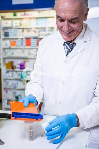 Pharmacist putting pills in container