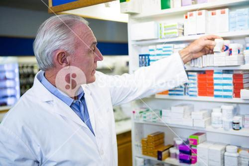 Pharmacist checking a bottle of drug