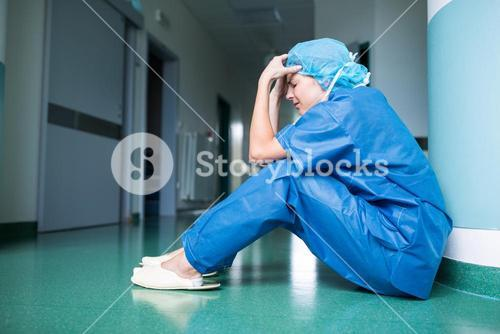 Sad surgeon sitting on floor in corridor