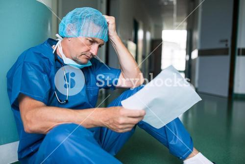 Sad surgeon sitting on floor with report in corridor