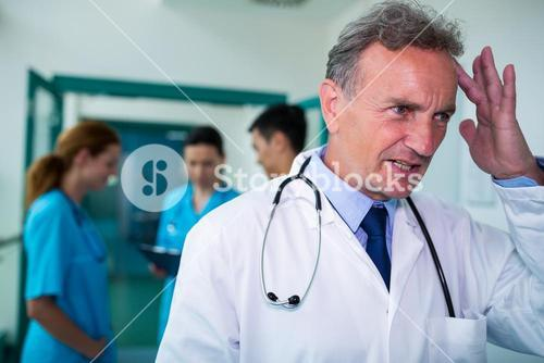 Tensed doctor standing in corridor