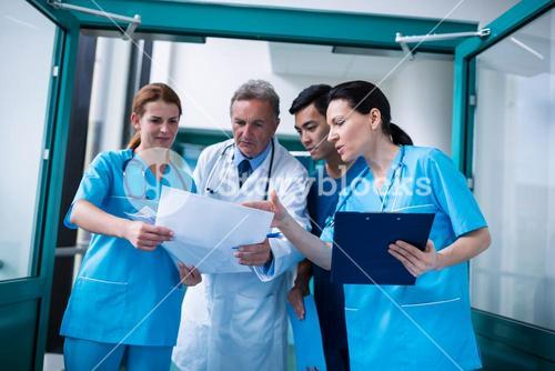Doctor and surgeons discussing with report in surgical room