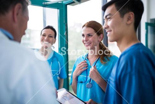Doctor and surgeons interacting wit each other in corridor