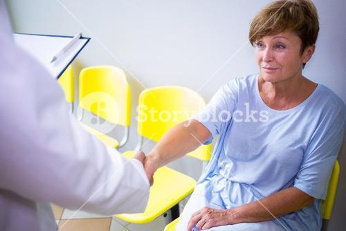 Doctor shaking hand with patient in waiting room