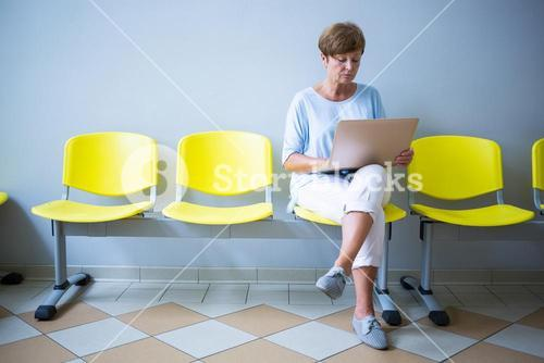 Patient sitting with report in a waiting room