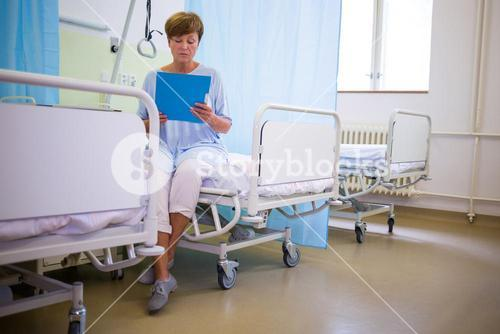 Senior patient sitting on a bed with report