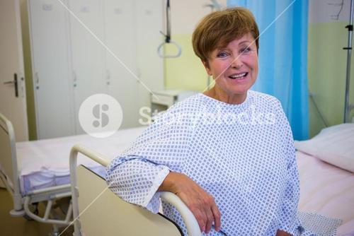 Portrait of smiling senior patient sitting on a bed