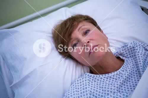 Portrait of sad senior patient lying on a bed