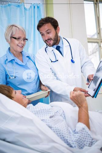 Doctors showing medical report to senior patient