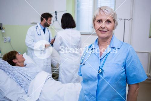 Portrait of nurse standing in hospital room