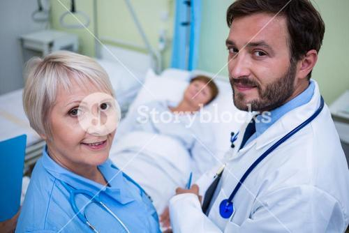 Portrait of doctor and nurse standing in hospital room