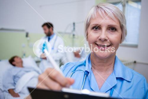 Portrait of smiling nurse writing on clipboard