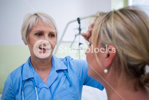 Nurse checking patient temperature