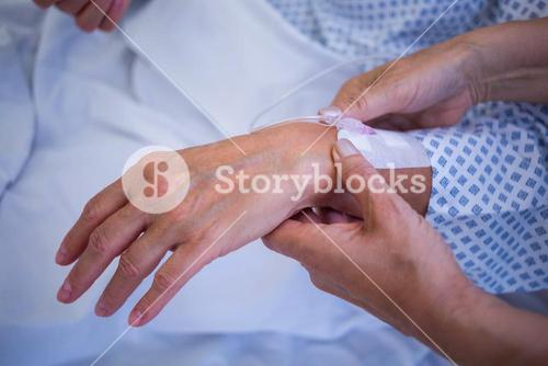 Nurse attaching iv drip on patient s hand