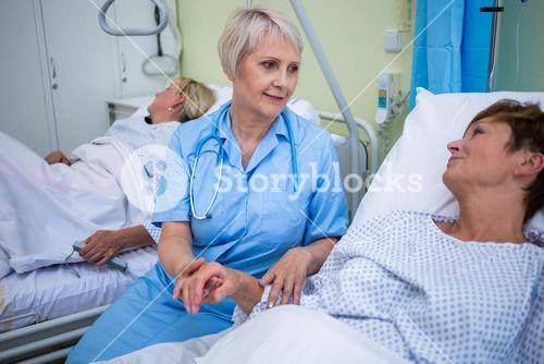 Nurse examining patients pulse