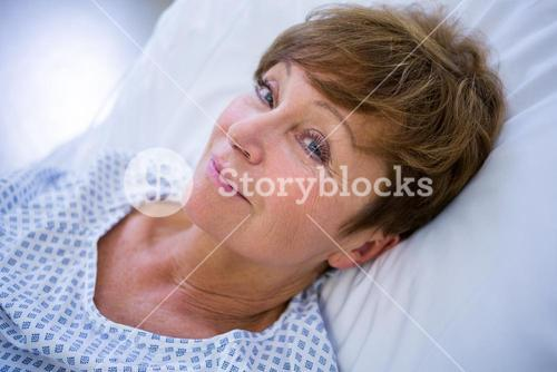 Portrait of smiling patient lying on bed