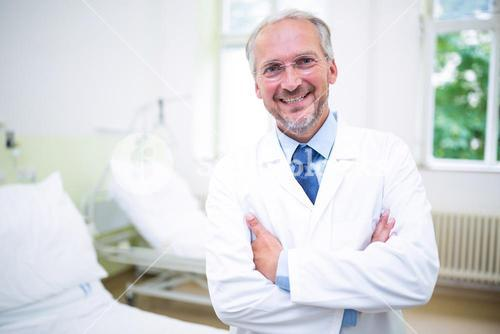 Smiling doctor standing with arms crossed