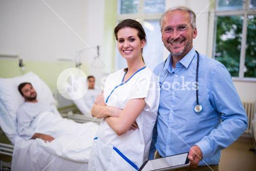 Smiling doctor and nurse standing in ward