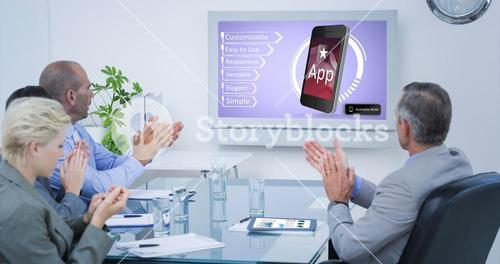 Composite image of business team applauding and looking at white screen